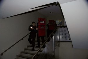 Low light and shield instructor - police officers SWAT indark on stairs in uniform