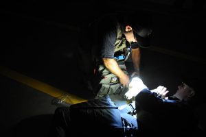 Low light instructor SWAT police doing medical care in the dark