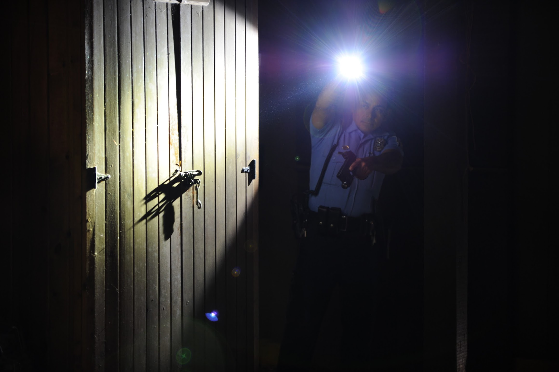 Low Lights Instructor Uniformed Police Officer with flashlight in the dark